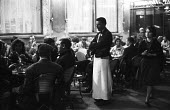 Waiter in cafe as customers drink, eat, sit and talk Paris 1961 - Romano Cagnoni - 1960s,1961,cafe,cafes,catering,cities,City,communicating,communication,conversation,customer,customers,dialogue,drink,drinking,drinks,EARNINGS,eating,EBF,Economic,Economy,employee,employees,Employment