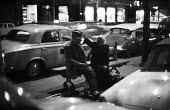 Homeless couple sitting on a street bench at night Paris 1961 - Romano Cagnoni - 1960s,1961,adult,adults,alcohol,AUTO,AUTOMOBILE,AUTOMOBILES,AUTOMOTIVE,bench,car,cars,cities,Citroen,City,couple,COUPLES,drink,excluded,exclusion,FEMALE,France,French,HARDSHIP,Homeless,HOMELESSNESS,im