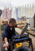 Woman drying her washing with a mangle outside her caravan 1962 travellers camp near Slough - Romano Cagnoni - 11-08-1962