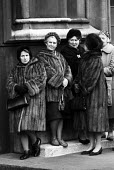 State Funeral of Sir Winston Churchill, London 1965. Woman wearing fur coats against the cold winter weather queue to view Churchills body Lying in State, Westminster Hall, Houses of Parliament - Romano Cagnoni - 1960s,1965,AFFLUENCE,AFFLUENT,against,bodies,body,Bourgeoisie,ceremonial,ceremonies,ceremony,cities,City,coat,coats,crowd,death,deaths,died,elite,elitism,EQUALITY,fashion,FEMALE,funeral,FUNERALS,fur,f