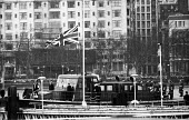 State Funeral of Sir Winston Churchill, London 1965. Cortege aboard The Havengore on the River Thames for his final journey watched by thousands lining the Embankment - Romano Cagnoni - 1960s,1965,armed forces,army,casket,ceremonial,ceremonies,ceremony,cities,City,coffin,coffin bearing,death,deaths,died,flag,flags,funeral,FUNERALS,grief,half mast,honor,honour,journey,JOURNEYS,London,