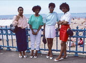 Four young women from London at Margate beach 1986. They joined thousands of others on the Whit Monday bank holiday - Martin Mayer - 1980s,1986,BAME,BAMEs,bank,BANKS,beach,BEACHES,black,BME,bmes,COAST,coastal,coasts,day out,Day Trip,diversity,ethnic,ethnicity,fashion,FEMALE,holiday,holiday maker,holiday makers,holidaymaker,holidaym