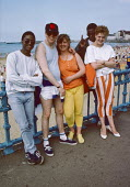 Young men annd women from London at Margate beach 1986. They joined thousands of others on the Whit Monday bank holiday - Martin Mayer - 1980s,1986,BAME,BAMEs,bank,BANKS,beach,BEACHES,Black,Black and White,BME,bmes,COAST,coastal,coasts,day out,Day Trip,diversity,ethnic,ethnicity,fashion,FEMALE,holiday,holiday maker,holiday makers,holid