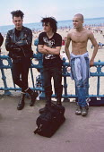 Punks and a skinhead on Margate beach 1986. They joined thousands of holidaymakers at the seaside on Whit Monday bank holiday - Martin Mayer - 1980s,1986,bank,BANKS,beach,BEACHES,COAST,coastal,coasts,day out,Day Trip,fashion,holiday,holiday maker,holiday makers,holidaymaker,holidaymakers,holidays,Leisure,LFL,LIFE,male,man,Margate,men,OCEAN,p