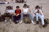 Four young lads on Margate beach 1986. Eating chips on Whit Monday bank holiday. - Martin Mayer - 1980s,1986,adolescence,adolescent,adolescents,bank,BANKS,beach,BEACHES,chips,COAST,coastal,coasts,day out,Day Trip,deckchair,deckchairs,Eating,food,FOODS,holiday,holiday maker,holiday makers,holidayma
