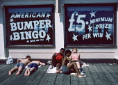 Young people sunbathing in Margate. They were under an American Bingo sign on Whit Monday bank holiday - Martin Mayer - 1980s,1986,American,americans,BAME,BAMEs,bank,BANKS,bingo,Black,Black and white,BME,bmes,COAST,coastal,coasts,day out,Day Trip,diversity,ethnic,ethnicity,FEMALE,Game of bingo,holiday,holiday maker,hol