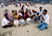 Sikh family on the beach in Margate 1986. They were among thousands enjoying the seaside on Whit Monday - Martin Mayer - 1980s,1986,adult,adults,Asian,Asians,BAME,BAMEs,beach,BEACHES,Black,BME,bmes,child,CHILDHOOD,children,COAST,coastal,coasts,DAD,DADDIES,DADDY,DADS,day out,Day Trip,deckchair,deckchairs,diversity,enjoyi