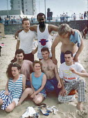 Young people on Margate main beach 1986. They joined thousands of other at the seaside on Whit Monday bank holiday - Martin Mayer - 1980s,1986,adolescence,adolescent,adolescents,BAME,BAMEs,bank,BANKS,beach,BEACHES,Black,Black and White,BME,bmes,COAST,coastal,coasts,day out,Day Trip,diversity,ethnic,ethnicity,fashion,FEMALE,holiday