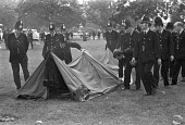 Police break up Windsor Free Festival after clashes, 1974. The pop festival was held annually from 1972-1974. Removing a tent - NLA - 1970s,1974,ACE,adult,adults,break,camping,clear up,clearing,CLJ,Culture,Festival,festivals,force,illegal,injunction,male,man,men,OFFICER,officers,PEOPLE,person,persons,police,Police Officer,policeman,