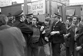 Police arrest pickets against The lump at a construction site, Mitcham, South London 1975 Severe industrial unrest caused by the use by SStanley Hugh Leach Ltd of lump labour delayed the housing const... - NLA - 1970s,1975,activist,activists,adult,adults,against,arrest,arrested,arresting,builder,builders,building site,Building Worker,building workers,CAMPAIGN,campaigner,campaigners,CAMPAIGNING,CAMPAIGNS,CLJ,C