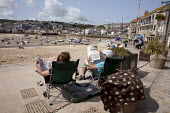 St Ives, Cornwall, a couple and their dog enjoying a relaxing time in the sunshine. - David Mansell - 2010s,2015,adult,adults,beach,beaches,chair,chairs,COAST,couple,COUPLES,enjoying,ENJOYMENT,FEMALE,holiday,holiday maker,holiday makers,holidaymaker,holidaymakers,holidays,Leisure,LFL,LIFE,male,man,men
