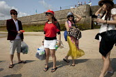 St Ives, Cornwall, Chinese friends who work in London on holiday together. The girls wearing hats and sunglasses to protect themselves from the sun - David Mansell - 17-07-2015