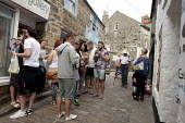 St Ives, Cornwall, narrow streets in the summer congested with tourists. Young people eating their Cornish Pasties - David Mansell - 2010s,2015,COAST,Cornish Pastie,Cornish Pasties,eat,eating,FEMALE,food,FOODS,holiday,holiday maker,holiday makers,holidaymaker,holidaymakers,holidays,Leisure,LFL,LIFE,male,man,men,people,person,person