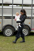 Horsmonden Gypsy Horse Fair, Kent. For a few hours it becomes an important social event for the Gypsy and Traveller community. A young Traveller mother carring her daughter. This Charter Fair dates ba... - David Mansell - 2010s,2015,2nd,adult,adults,babies,baby,child,CHILDHOOD,children,Domesticated Ungulates,EARLY YEARS,equestrian,equine,Fair,families,family,female,females,gipsey,Gipsey Gipsy Gypsey,Gipsies,Gipsy,girl,