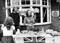 Silver Jubilee of Queen Elizabeth II 1977. Tea stall, street party Ruslip, London - David Mansell - 1970s,1977,2nd,cities,City,COMMEMORATE,COMMEMORATING,commemoration,COMMEMORATIONS,commemorative,communities,community,Elizabeth,FEMALE,flag,flags,highway,Leisure,LFL,LIFE,London,male,man,men,Monarchy,