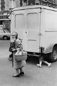 Woman and mannequin figure under a van, Paris, France 1980 - David Mansell - 1980,1980s,age,ageing population,bought,buy,buyer,buyers,buying,cities,City,commodities,commodity,consumer,consumers,customer,customers,EBF,Economic,Economy,elderly,FEMALE,figure,figures,France,french