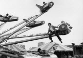 Fairground worker riding the ride, Hayes Carnival West London 1978. Compressed air Jet roundabout - David Mansell - 1970s,1978,adolescence,adolescent,adolescents,amusement park,child,CHILDHOOD,children,cities,City,EARNINGS,EBF,Economic,Economy,employee,employees,Employment,fair,fairground,female,females,Funfair,gir