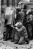 Rioting, The Bogside, Derry, Northern Ireland 1979 A soldier firing baton rounds with a Swastika scratched on the side of his helmet- strongly associated with fascism and nazism. Rioting started in th... - David Mansell - 04-08-1979