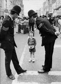 Two Police Sergeants talking to a little girl, Notting Hill Carnival 1978 - David Mansell - on the beat,1970s,1978,ACE,adult,adults,assisting,beat,carnival,Carnivals,child,CHILDHOOD,children,cities,City,CLJ,communicating,communication,community policing,confidence patrol,conversation,Culture