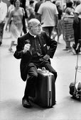 American vicar smoking a cigarette, waiting at Victoria Railway Station, London 1983 - David Mansell - 1980s,1983,american,americans,bag,bags,Belief,Catholic,catholicism,Catholics,christian,christianity,christians,CIGARETTE,cigarettes,cities,City,clergy,concourse,conviction,EBF,Economic,Economy,faith,G