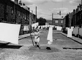 Woman hanging out washing across the street, Keighley, Yorkshire 1977 - David Mansell - 1970s,1977,apparel,backstreet,backstreets,clothes,clothing,cobbled street,Council Housing,Council Housing,FEMALE,hanging,highway,home,homes,house,houses,housework,housing,Housing Estate,people,person,
