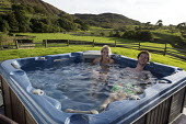 Enjoying an outdoor hot tub, Holday cottage, Cumbria - John Harris - 2010s,2016,adult,adults,cottage,COTTAGES,couple,COUPLES,Enjoying,ENJOYMENT,FEMALE,holiday,holiday maker,holiday makers,holidaymaker,holidaymakers,holidays,Leisure,LFL,LIFE,Lifestyle,male,man,men,outdo