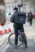 Ubereats delivery worker, Birmingham - John Harris - 2010s,2018,app,application,applications,apps,backpack,bicycle,bicycles,BICYCLING,Bicyclist,Bicyclists,BIKE,BIKES,Birmingham,by hand,carries,carry,carrying,CELLULAR,cities,city,collecting,contracts,Cou