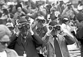Spectators watching a horse race with binoculars, Newmarket racecourse, Suffolk 1975 - NLA - 1970s,1975,AFFLUENCE,AFFLUENT,bet,bets,betting,BINOCULAR,binoculars,Bourgeoisie,Domesticated Ungulates,elite,elitism,equestrian,gambling,high,high income,horse,horse race,Horse racing,horserace,horser