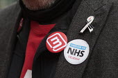 Momentum supporter NHS in Crisis - Fix it Now protest, Gloucestershire - John Harris - 2010s,2018,activist,activists,against,badge,badges,CAMPAIGN,campaigner,campaigners,CAMPAIGNING,CAMPAIGNS,Crisis,DEMONSTRATING,Demonstration,DEMONSTRATIONS,Labour Party,Left,left wing,Leftwing,Momentum
