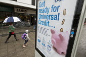 Pedestrians walking past a Get Ready For Universal Credit advertisment, Gloucester city centre. Coins dropping into a piggy bank - John Harris - 2010s,2018,adolescence,adolescent,adolescents,adult,adults,advertisement,advertisements,Austerity Cuts,bag,bags,bank,BANKS,BENEFIT,Benefit cuts,Benefits,bought,buying,change,child,Child Tax Credit,CHI