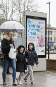 Pedestrians walking past a Get Ready For Universal Credit advertisment, Gloucester city centre. Coins dropping into a piggy bank - John Harris - 2010s,2018,adult,adults,advertisement,advertisements,Austerity Cuts,bag,bags,bank,BANKS,BENEFIT,Benefit cuts,Benefits,BLK1,bought,boy,boys,buy,buyer,buyers,buying,change,child,Child Tax Credit,CHILDHO