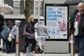 Pedestrians walking past a Get Ready For Universal Credit advertisment, Gloucester city centre. Coins dropping into a piggy bank - John Harris - 2010s,2018,advertisement,advertisements,Austerity Cuts,bank,BANKS,BENEFIT,Benefit cuts,Benefits,change,Child Tax Credit,cities,City,coin,Coinage,coins,cost of living,credits,government,housing benefit