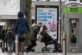 Pedestrians walking past a Get Ready For Universal Credit advertisment, Gloucester city centre. Coins dropping into a piggy bank - John Harris - 2010s,2018,advertisement,advertisements,age,ageing population,Austerity Cuts,bank,BANKS,BENEFIT,Benefit cuts,Benefits,bound,CARE,carer,carers,change,Child Tax Credit,cities,City,coin,Coinage,coins,cos