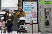 Pedestrians walking past a Get Ready For Universal Credit advertisment, Gloucester city centre. Coins dropping into a piggy bank - John Harris - 03-02-2018