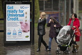Pedestrians walking past a Get Ready For Universal Credit advertisment, Gloucester city centre. Coins dropping into a piggy bank - John Harris - 2010s,2018,adult,adults,advertisement,advertisements,Austerity Cuts,bank,BANKS,BENEFIT,Benefit cuts,Benefits,bought,boy,boys,buying,change,child,Child Tax Credit,CHILDHOOD,children,cities,City,coin,Co
