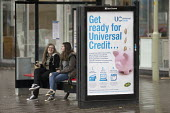 Passengers waiting at a bus stop with a Get Ready For Universal Credit advertisment, Gloucester city center. Coins dropping into a piggy bank - John Harris - 2010s,2018,advertisement,advertisements,Austerity Cuts,bank,BANKS,BENEFIT,Benefit cuts,Benefits,bus,bus service,Bus Stop,BUSES,change,Child Tax Credit,cities,City,coin,Coinage,coins,cost of living,cre