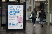 Pedestrians walking past a Get Ready For Universal Credit advertisment, Gloucester city centre. Coins dropping into a piggy bank - John Harris - 2010s,2018,advertisement,advertisements,Austerity Cuts,bag,bags,bank,BANKS,BENEFIT,Benefit cuts,Benefits,change,Child Tax Credit,cities,City,coin,Coinage,coins,cost of living,credits,government,housin