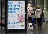 Pedestrians walking past a Get Ready For Universal Credit advertisment, Gloucester city centre. Coins dropping into a piggy bank - John Harris - 2010s,2018,adult,adults,advertisement,advertisements,Austerity Cuts,bag,bags,bank,BANKS,BENEFIT,Benefit cuts,Benefits,bought,boy,boys,buying,change,child,Child Tax Credit,CHILDHOOD,children,cities,Cit