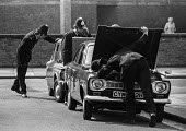 Police searching cars near Lambeth Magistrates Court, London 1973 during the trial of the Belfast 10 on charges made after the London bomb explosions on March 8 - Peter Arkell - 1970s,1973,adult,adults,AUTO,AUTOMOBILE,AUTOMOBILES,AUTOMOTIVE,Belfast 10,bomb,bombs,bonnet,car,cars,check,checking,CLJ,conflict,court,court case,courts,device,devices,escort,explosive,explosives,forc