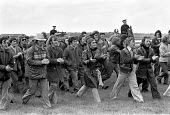 Stable lads strike for a living wage, Newmarket races 1975 pickets halt the races, disrupting the event by marching round the racecourse - Martin Mayer - 1970s,1975,activist,activists,CAMPAIGNING,CAMPAIGNS,course,courses,DEMONSTRATING,Demonstration,DISPUTE,disputes,Domesticated Ungulates,EARNINGS,equestrian,horse,horse race,horse racing,horserace,horse