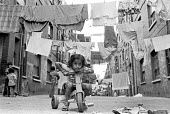 Bangladeshi children playing, washing lines, East End London 1973 - Katalin Arkell - 1970s,1973,apparel,backstreet,backstreets,child,childhood,children,cities,City,clothes,clothing,Council Housing,Council Housing,Diaspora,drying out,East End,excluded,exclusion,female,females,foreign,g