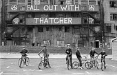 Youth on bicycles, Royal Tunbridge Wells, Kent, 1983. Derelict building with CND graffiti Fall Out With Thatcher - Katalin Arkell - peace movement,1980s,1983,activist,activists,adolescence,adolescent,adolescents,bicycle,bicycles,BICYCLING,Bicyclist,Bicyclists,BIKE,BIKES,boy,boys,building,BUILDINGS,Campaign for nuclear disarmament,