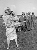 Posing for a photograph, Derby Day, Epsom Downs Racecourse Surrey 1982 Top hat and tails - Katalin Arkell - 1980s,1982,AFFLUENCE,AFFLUENT,amateur,AUTO,AUTOMOBILE,AUTOMOBILES,AUTOMOTIVE,Bourgeoisie,camera,cameras,car,car park,cars,Derby day,Domesticated Ungulates,elite,elitism,equestrian,equine,FEMALE,hat,ha