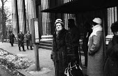Woman in a fur coat waiting at a bus stop, Euston Road London winter 1963 - Alex Low - 28-01-1963