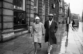 Well dressed black couple walking arm in arm, rain drenched Piccadilly early morning London 1957 - Alan Vines - 29-11-1957