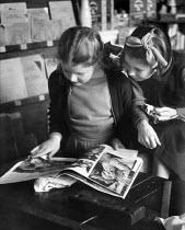 Primary school pupils reading a magazine, London 1949 - Elisabeth Chat - 1940s,1949,child,CHILDHOOD,children,cities,City,class,classroom,classrooms,EDU,educate,educating,Education,educational,female,females,friend,friends,friendship,friendships,girl,girls,interested,intere