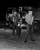 Toxteth riots, Liverpool 1981 Rioters pose with a police shield and baton in front of a burnt out fire engine - John Harris - 1980s,1981,adult,adults,BAME,BAMEs,black,Black and White,BME,BME black,bmes,burnt,cities,City,civil unrest,CLJ crime law and justice,conflict,Conflicts,conflicts conflict,diversity,engine,ENGINES,ethn