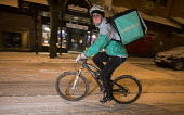 Deliver cyclists working on the snow covered streets of Bristol. - Paul Box - 2010s,2018,bicycle,bicycles,BICYCLING,Bicyclist,Bicyclists,BIKE,BIKES,cities,City,cold,cycle,cycles,cycling,Cyclist,Cyclists,Deliver,deliveries,delivering,Deliveroo,delivery,EARNINGS,EBF,Economic,Econ