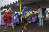 Big Island, Hawaii, Saturday Makuu Farmers Market, Pahoa, a town with many people living alternative lifestyles - David Bacon - 2010s,2018,African American,alternative lifestyle,BAME,BAMEs,Black,BME,bmes,bought,buy,buyer,buyers,buying,commodities,commodity,consumer,consumers,customer,customers,diversity,ethnic,ethnicity,famili
