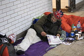 Homeless man with Union Jack London hat, Westminster, London. Reading a story in the Evening Standard newspaper - Jess Hurd - 09-03-2018
